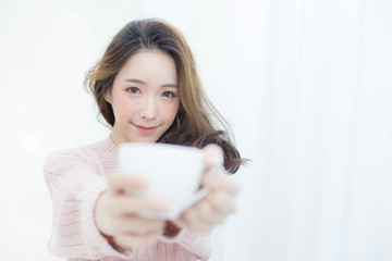 Asian Woman holding coffee cup at bedroom. People lifestyle concept.