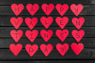 Greetings with Valentine's day on red paper hearts, top view