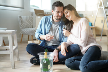 Couple cheering with champagne in new home