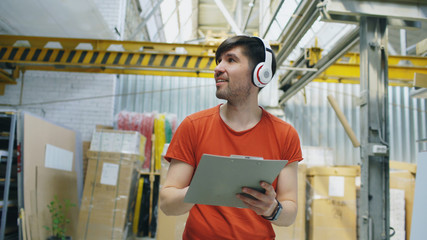 Happy young worker in industrial warehouse listening to music during work. Man in headphones have fun at workplace.