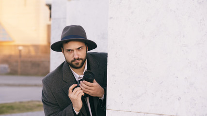 Young male spy agent wearing hat and coat photographing criminal people and hiding behind the wall
