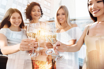 Alcoholic drinks. Selective focus of glasses with champagne being held by nice beautiful delighted women