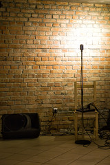 A microphone ready on stage against a brick wall ready for the Karaoke performer
