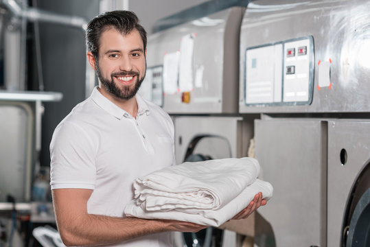 happy dry cleaning worker holding stack of clean clothes