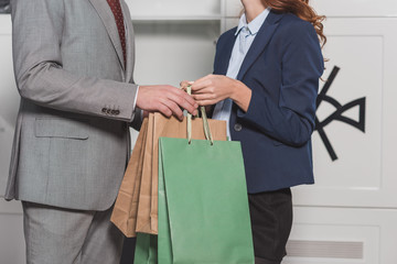 cropped shot of dry cleaning manageress giving paper bags to customer