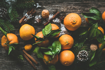 Tangerines or clementines, spices, nuts and pine cones. Winter holidays composition on wooden background. Top view, toned image
