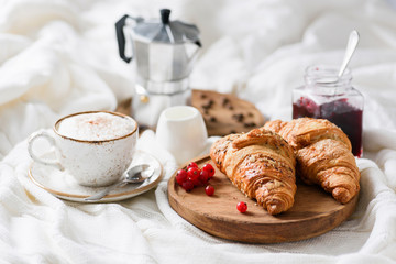 Breakfast in bed with croissants, jam, coffee cappucino with cream and milk foam. Horizontal view