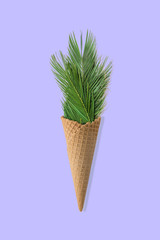Palm tree leaves in ice cream cone on blue background. Flat lay. Summer tropical concept.