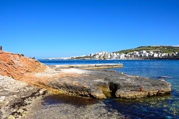 Rocky shoreline with views across the bay towards St Pauls Bay,  Xenxija Bay, Malta.