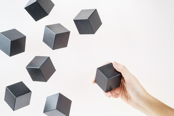 Black wooden cubes are floating. A woman's hand takes a floating cube.  Concept of creative, logical thinking. Abstract background with cubes with copy space. Floating shapes.