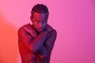 Young black man posing in purple background
