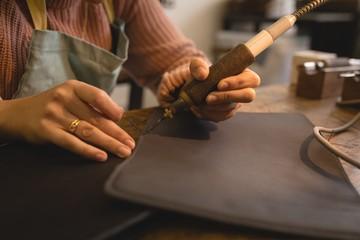 Worker stitching leather with stitching machine