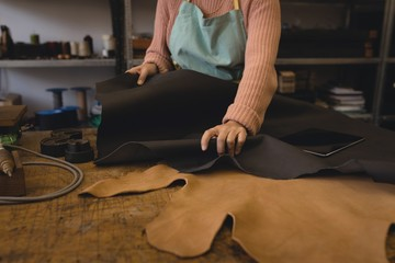 Worker holding leather in workshop