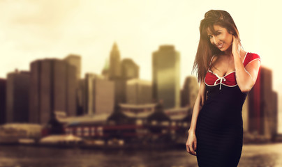 Beautiful young woman wearing a dress in front of a big city