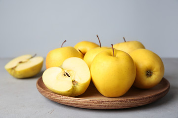 Fototapete - Wooden plate with ripe yellow apples on table