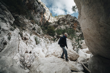 Aged Man hiking insdide the deepest canyon  in Europe - Activity and Health concept - Sardinia