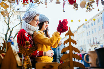 Couple in knitted clothes hugging outside, choosing a souvenirs and having fun in winter christmas fair decorations at square of the european city. Girl holding glass ball. Vacation, holiday concept