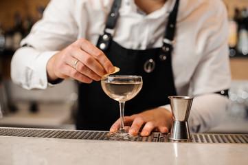 Barman adding a lemon peel into a cocktail glass