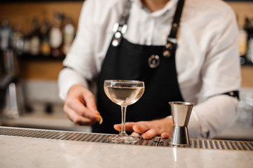 Barman with an elegant glass filled with drink