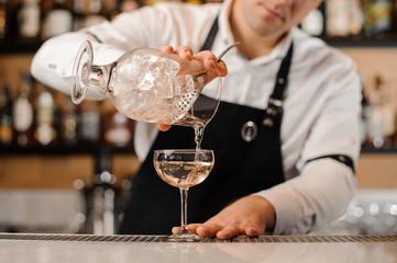 Bartender adding vodka into a cocktail glass