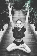 Brunette girl do yoga in garden, jungle near the pool. yoga pose sitting