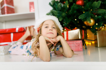 Photo of girl in Santa cap lying on floor