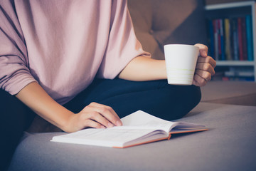 Unrecognizable woman enjoying in coffee time with a book.