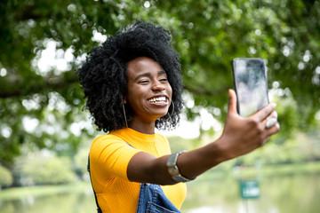 Afro girl descent taking selfie photos in the park