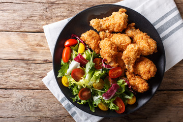 deep-fried chicken wings in breadcrumbs and fresh vegetable close-up. horizontal top view
