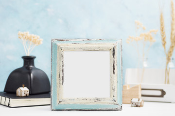 Blue wooden Photo frame mock up with plants in vase, ceramic decor on shelf. Scandinavian style. Text space