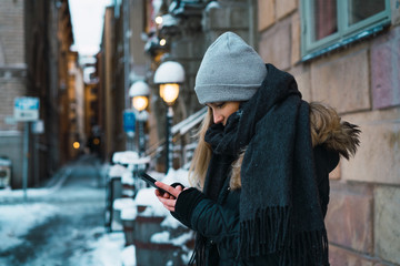 Woman with smartphone on winter street