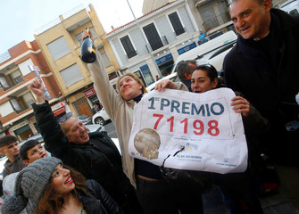 """Neringa Bertolite from Lithuania, celebrates after buying one of the winning tickets of the biggest prize of Spain's Christmas Lottery """"El Gordo"""" (The Fat One) in Benetusser"""