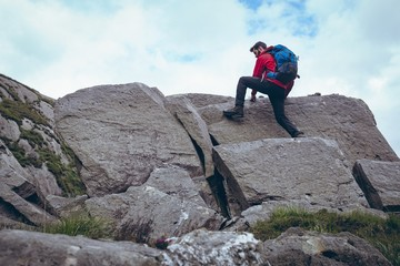 Male hiker climbing the rocks