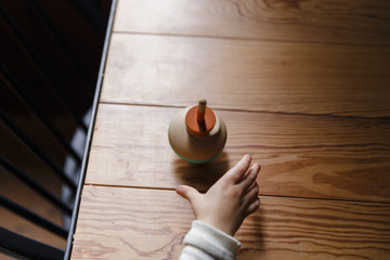 A spinning top on a wooden table. A toddler is reaching for the toy.