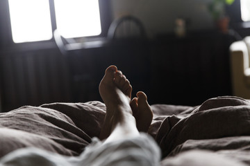 Bare feet in a bed, seen in first person.