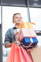 happy boy holding colored boxes with paper bags in hands at shop interior