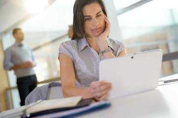 Portrait of businesswoman in office working on digital tablet
