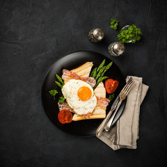 Overhead shot of breakfast or lunch with fried egg, bread toast, green asparagus, tomatoes and bacon on black plate with copy space.