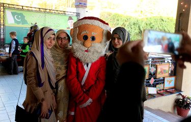Women pose for a photo with a man dressed in a Santa Claus costume during Christmas celebrations in Islamabad