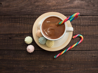 Cocoa with foam, sweet candy and colored bisse on a wooden table
