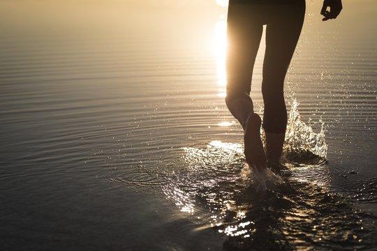 Woman in wetsuit walking in shallow water