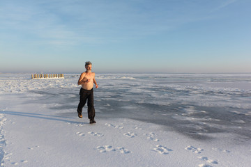 Elderly man with a naked torso  cold conditioning during  a run on the frozen river in winter