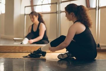 Irish dancer sitting front of mirror on floor tying her shoelace