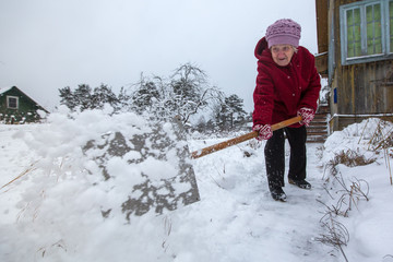 An elderly woman cleans the snow near his home in the village.