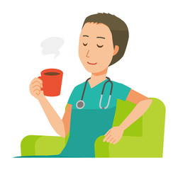 A male doctor wearing a green scrub sits on the sofa and is drinking coffee
