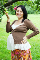 happy young pregnant woman has a walk in a summer apple garden
