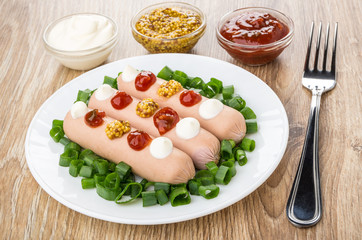 Sausages with scallion in plate, bowls with sauces and mustard