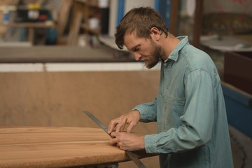 Man measuring with ruler on surfboard
