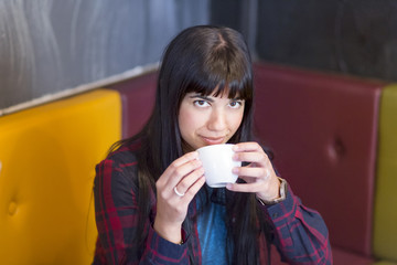 Ragazza mora con camicia a quadri aperta e maglietta sorseggia la sua tisana in una tazza seduta su dei divani colorati