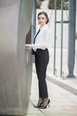 Figura intera  di una manager donna con camicia bianca e pantalone nero che scrive al cellulare in esterni